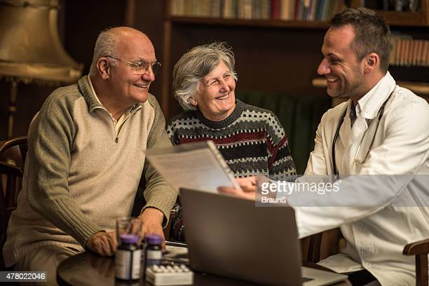 Happy doctor talking to senior couple about some medical documents.