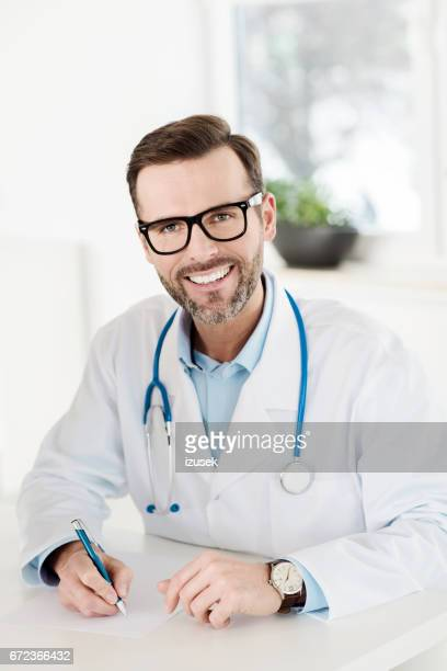 happy doctor using laptop in an office - izusek stock pictures, royalty-free photos & images