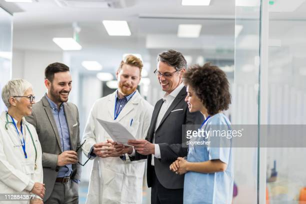 happy doctors and businessmen reading medical data in hospital. - group of doctors stock pictures, royalty-free photos & images