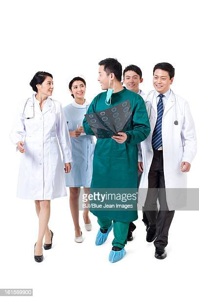 Happy doctors and nurse with X-ray plate in hand walking and talking
