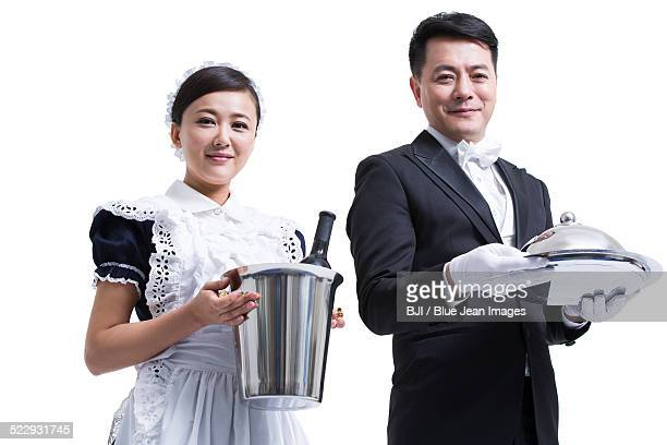 Happy domestic staff serving food and drink