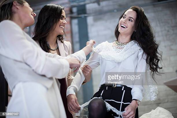 Happy dressmakers with client trying on wedding dress