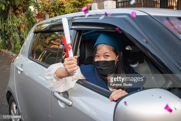 happy east asian graduate showing her rolled up certificate - parade stock pictures, royalty-free photos & images