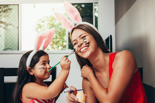 Happy easter! A mother and her daughter painting Easter eggs. Happy family preparing for Easter. Cute little child girl wearing bunny ears on Easter day 1132288745