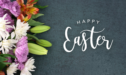 Happy Easter calligraphy over blackboard background with colorful flower blossom bouquet 929742898