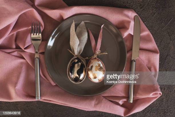 happy easter concept. top view of golden egg with ribbon in the white plate with silver fork and knife - golden egg restaurant stock pictures, royalty-free photos & images