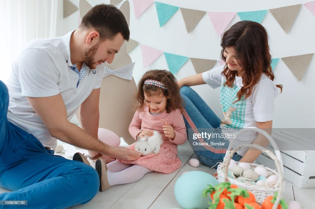 Happy easter family playing with rabbit in decorated studio interior : Stock Photo