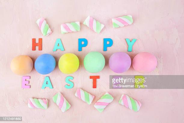 happy easter text with colorful eggs and marshmallows on pink background - top view - happy easter text stock pictures, royalty-free photos & images