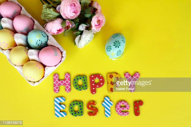 """happy easter"" text with easter eggs and decoration over yellow background - easter photos stock pictures, royalty-free photos & images"