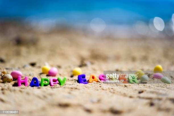 happy easter writing on beach sand - easter beach stock pictures, royalty-free photos & images