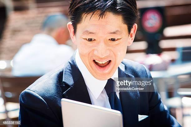 うっとりするような日本の実業家のタブレットを見ている屋外