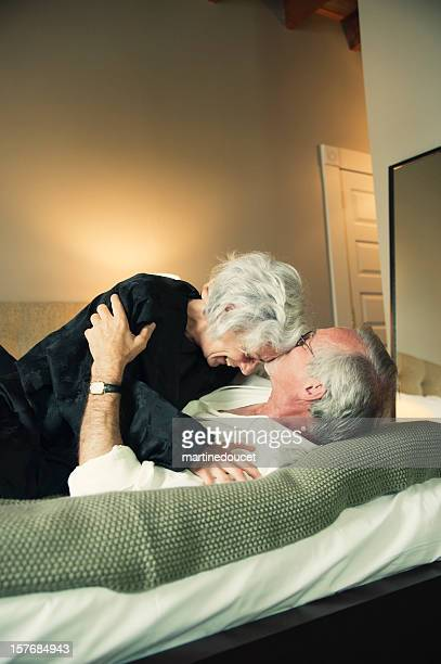 happy elderly couple laughing in bed