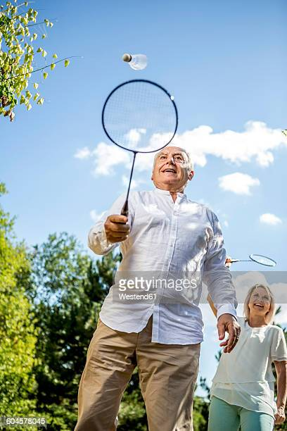 Happy elderly couple playing badminton outdoors