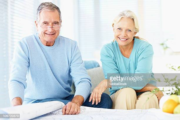 Happy elderly couple sitting with blue prints of new property