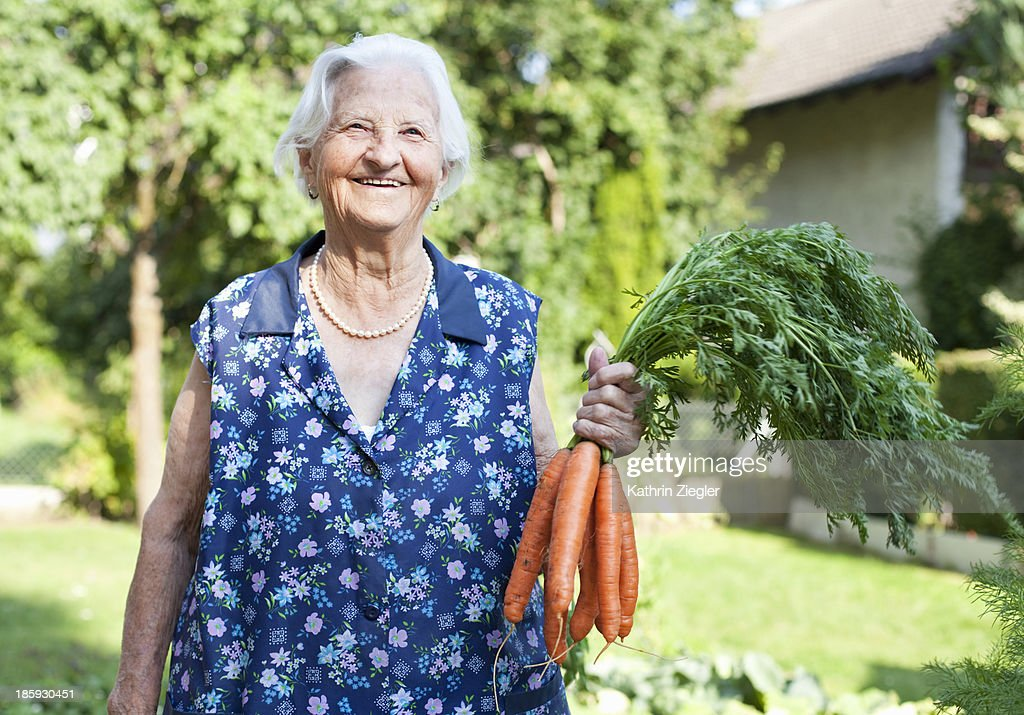 happy elderly lady holding a bunch of carrots : Stock Photo
