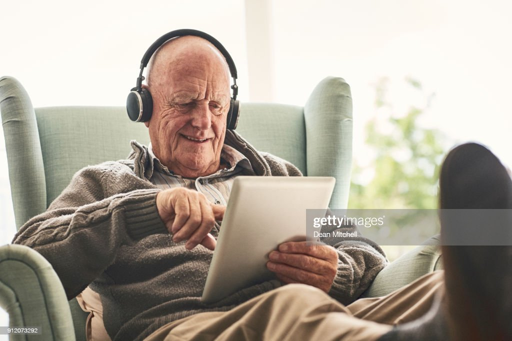 Happy elderly man at home using digital tablet : Stock Photo