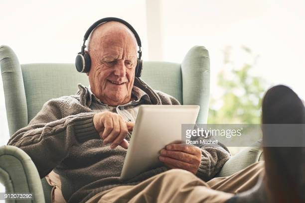 happy elderly man at home using digital tablet - senior adult stock pictures, royalty-free photos & images