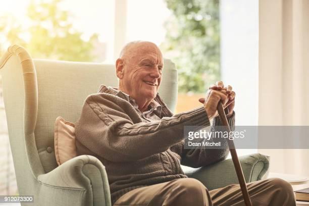 glücklich älterer mann sitzt zu hause - fotostock stock-fotos und bilder