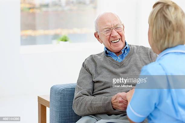 Happy elderly patient talking with nurse at home