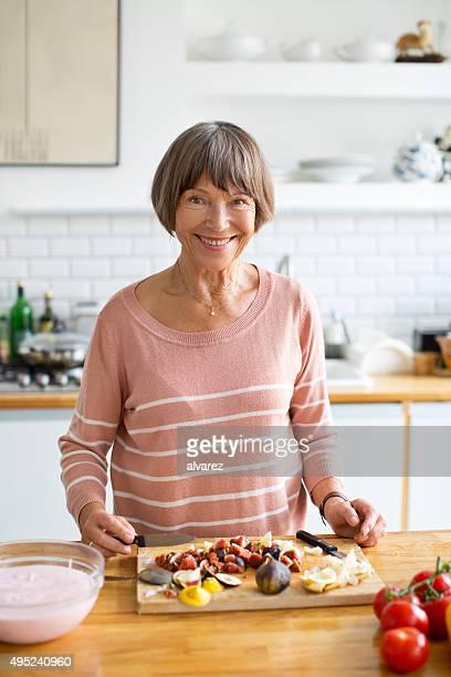 Happy elderly woman cooking in kitchen