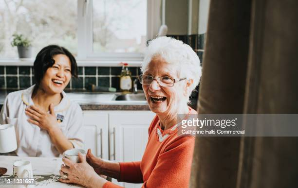 a happy elderly woman during a carers home visit - smiling stock pictures, royalty-free photos & images