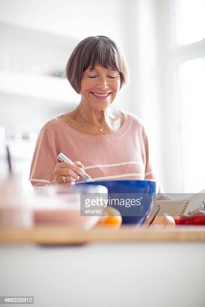 Happy elderly woman in kitchen cooking food