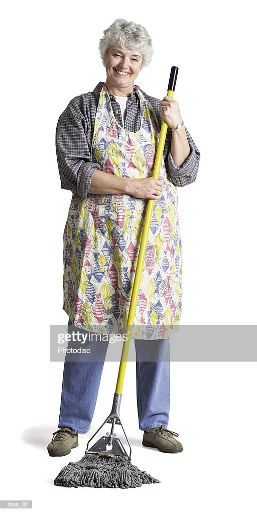 Happy elderly woman wearing an apron mops the floor. : Foto de stock