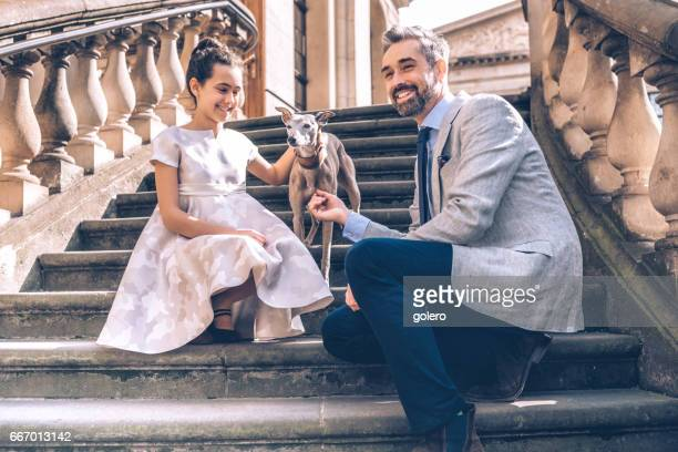happy elegant father sitting on stairs with festive dressed teenage girl and dog