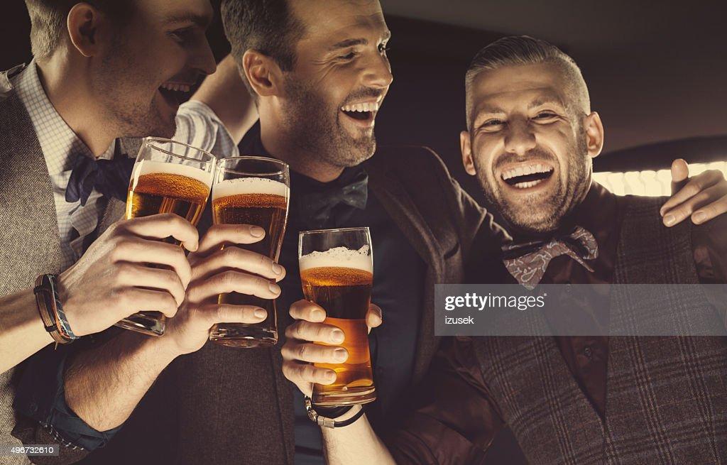 Happy elegant men toasting with beer : Stock Photo