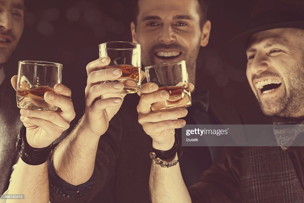 Happy elegant men toasting with whiskey : Stock Photo