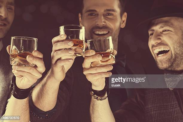 happy elegant men toasting with whiskey - honour stock pictures, royalty-free photos & images