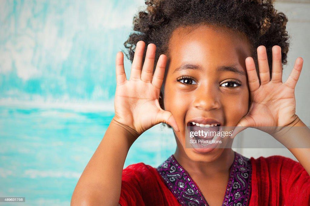 Happy elementary age Ethiopian girl making face at camera : Stock Photo