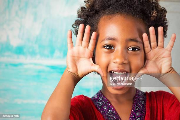 Glückliches Kind im Grundschulalter Äthiopischer Mädchen machen Gesicht in die Kamera