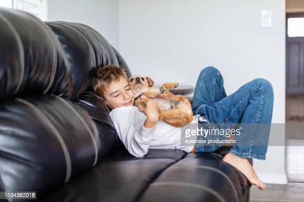 happy elementary aged blonde boy active and content at home with pet dog - schulkind nur jungen stock-fotos und bilder