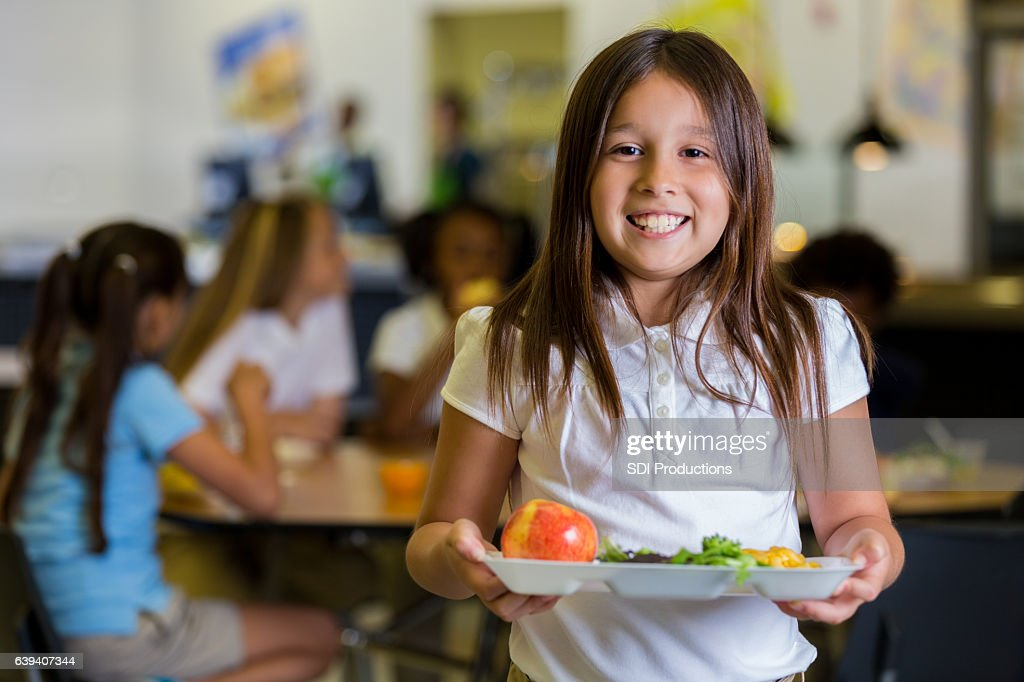 Happy elementary school girl with healthy food in cafeteria : Foto de stock