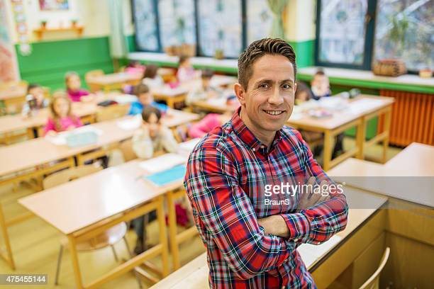 Happy elementary school teacher with crossed arms in the classroom.