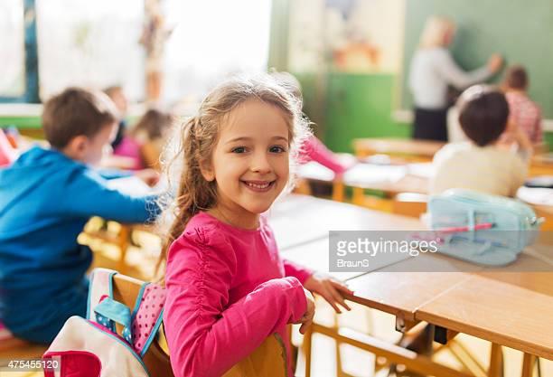 Aluna feliz durante uma aula da escola primária em sala de aula.