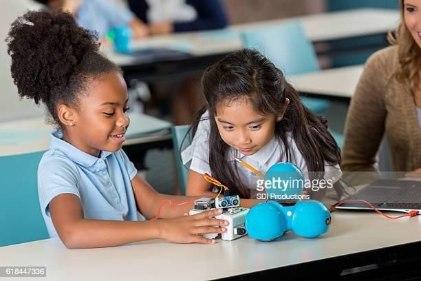 Happy elementary schoolgirls work on robotics project