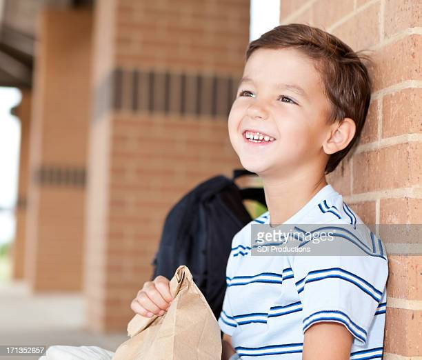Happy elementary student at school with his lunch bag
