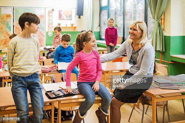 Happy elementary teacher communicating with her students on a break.
