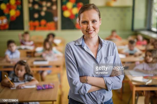 enseignants du primaire heureux avec les bras croisés en classe. - enseignante photos et images de collection