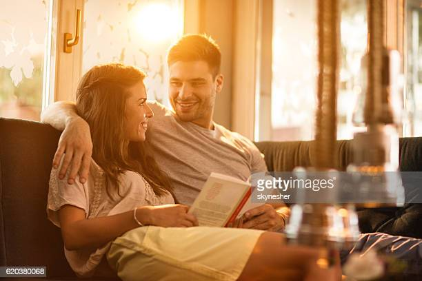 Happy embraced couple at home reading a book together.