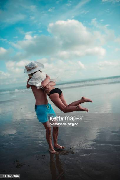 Happy Embraced Couple Having Fun and Spinning on the Beach