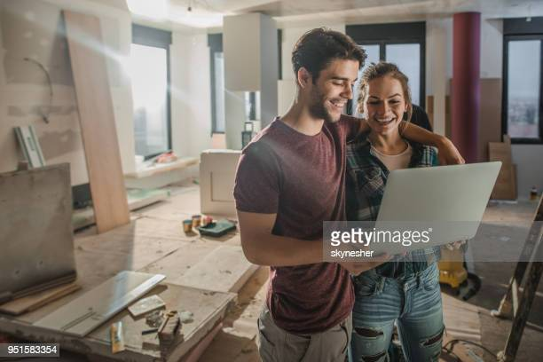 Happy embraced couple using laptop while being on construction site in their apartment.