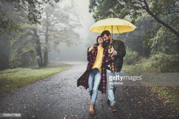happy embraced couple walking with umbrella at foggy forest. - rain stock pictures, royalty-free photos & images