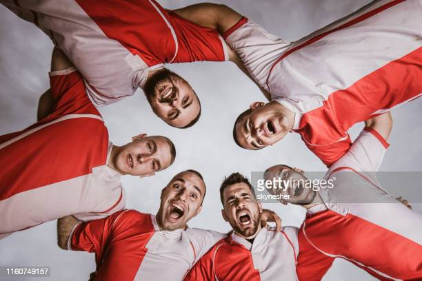 happy embraced sports team shouting against the sky. - rugby team stock pictures, royalty-free photos & images