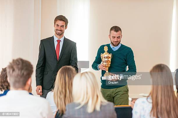 Happy employee of the month receives trophy from manager