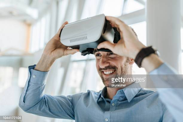 happy entrepreneur having fun while using virtual reality simulator. - virtual reality simulator stock photos and pictures