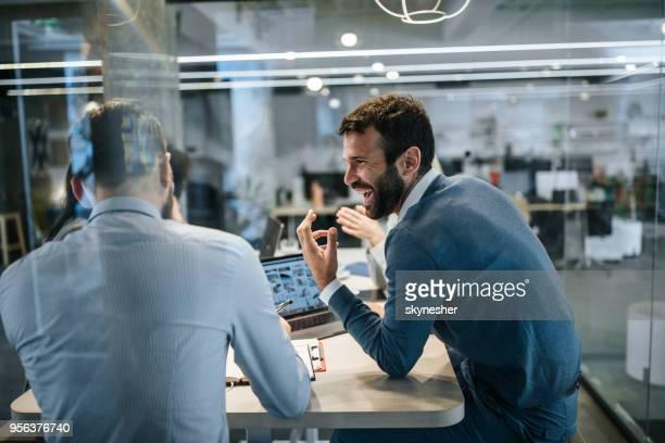 glückliche unternehmer im gespräch mit seinem kollegen auf einem treffen im büro. - ingenieur stock-fotos und bilder