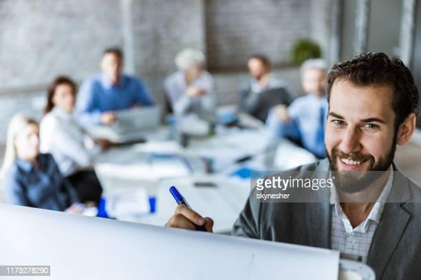 glücklicher unternehmer, der während eines meetings im büro geschäftspläne auf whiteboard schreibt. - erwachsene person stock-fotos und bilder